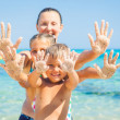 Family playing on sandy beach — Stock Photo
