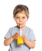 Portrait of little boy drinking orange juice — Stock Photo