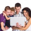 Stock Photo: Young parents, with children, on laptop computer