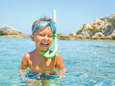 Cute boy playing in the sea — Stock Photo