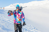 Young man with skis and a ski wear — Stock Photo