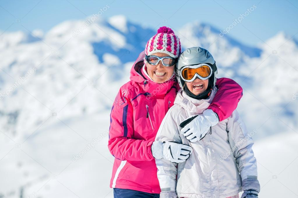 Happy smiling girl in ski goggles and with her mother, Zellertal, Austria. Focus on the girl  Stock Photo #15912471