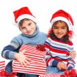 Little kids in Santa's hat with gift box — Stock Photo #16276319