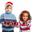 Kids in Santa's hat holding a christmas ball — Stock Photo #16307587