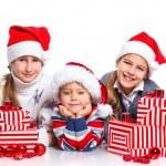 Happy kids in Santa's hat with gift box — Stock Photo #16320933