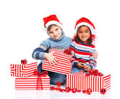 Little kids in Santa's hat with gift box — Stock Photo