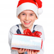 Little boy in Santa's hat with gift box — Stock Photo #16929403