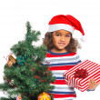 Little girl in Santa's hat with gift box — Stock Photo