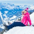 Young skier sitting on the hill - Stok fotoğraf