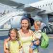 Young mother with two kids in front of airplane — Stock Photo