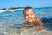 Portrait of young boy swimming in the transparent sea — Stock Photo