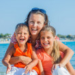 Portrait of happy family laughing and looking at camera on the beach — Stock Photo #19206975