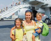 Mladá matka s dvěma dětmi před letadlo — Stock fotografie