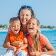 Portrait of happy family laughing and looking at camera on the beach — Stock Photo #19295531