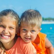Smiling happy brother and sister posing on a beach. In the background the sea — Stock Photo