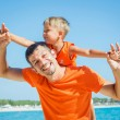 Clouseup portrait of happy father with son laughing and looking at camera on the beach — Stock Photo
