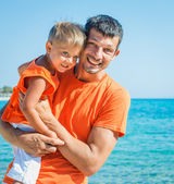 Clouseup retrato del padre feliz con hijo riendo y mirando a cámara en la playa — Foto de Stock