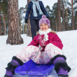 Cute girl on sleds with her mother in snow forest. — Stock Photo #19527537