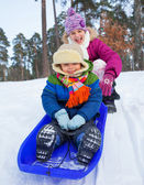 Cute sister and brother on sleds in snow forest. Focus on the boy — Stock Photo