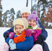 Mother with her two kids is sledging in winter-landscape. Focus on the boy. — Stock Photo