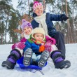 Two kids is sledging with mother in winter-landscape. Focus on the boy. — Stock Photo