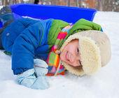 Süße kleine junge auf schlitten im schnee wald. — Stockfoto