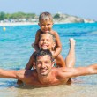 Father with his kids have fun and swim sea — Stock Photo