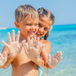 Stock Photo: Closeup view of hands by the girl and boy on the sand beach