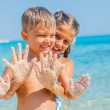 Closeup view of hands by the girl and boy on the sand beach — Stock Photo