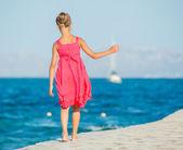 Girl walking on jetty — Stock Photo
