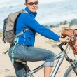 Woman with bike on the beach — Stock Photo