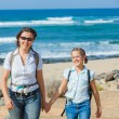 Mother with her daughter walking on a beach. — Stock Photo