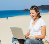 Woman sitting on beach with laptop — Stock Photo