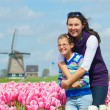 Постер, плакат: Boy with mother in the tulips field