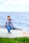 Cute little boy sitting on the boat — Foto Stock
