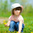 Girl sitting among dandelions — Stock Photo