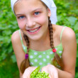 Stock Photo: Portrait of beautiful girl holding green peas in garden