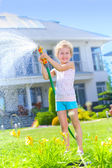 Little girl watering flowers — Stockfoto