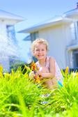 Little girl watering flowers — Stock Photo