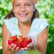 Young girl holding in hand organic natural healthy food produce - strawberries. Vertical view — Stock Photo