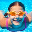 The cute girl swimming underwater and smiling — Stock Photo #27246783