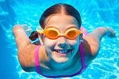 Cute girl pływanie pod wodą i uśmiechając się — Zdjęcie stockowe