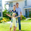 Happy family on the lawn in front of his new cottage — Stock Photo