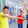 Portrait of happy teens boy with his friends by painted wall looking at camera. Vertical view — Stock Photo