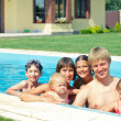 Summer vacation. Happy family with four kids in swimming pool outdoors — Stock Photo
