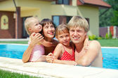 Summer vacation. Happy family of four in swimming pool outdoors — Stock Photo
