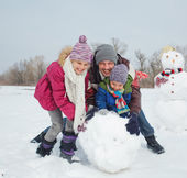 Family make a snowman — Stock Photo
