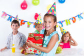 Girl with giftbox at birthday party — Stock Photo