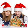 Girls in Santa's hat with gingerbread house — Stock Photo