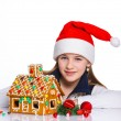 Girl in Santa's hat with gingerbread house — Стоковая фотография